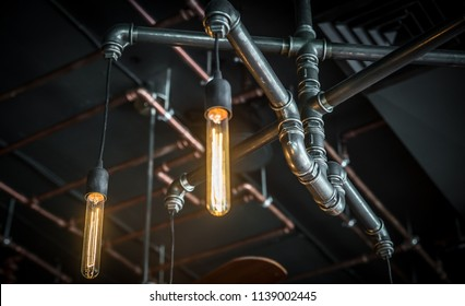 Pipes, fittings and lamp on dark background