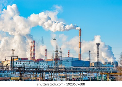 The pipes of the metallurgical plant, from which dirty smoke rises into the clear sky. Air pollution! Exhaust gases, depletion of the ozone layer,the greenhouse effect. An environmental disaster. - Shutterstock ID 1928659688
