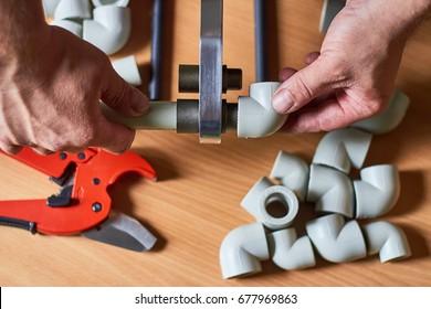 Pipes of sanitary engineering welded plastic. Ppr Pipe welding tool. Work plumber