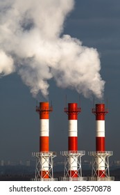 Pipes of a thermal power plant with a smoke against a city landscape