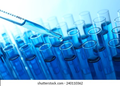 Pipette adding blue fluid to the one of test-tubes on light background