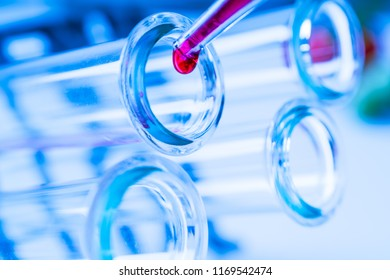 Pipette adding fluid to one of several test tubes .medical glassware