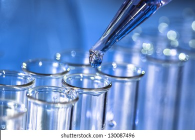 Pipette adding fluid to one of several test tubes