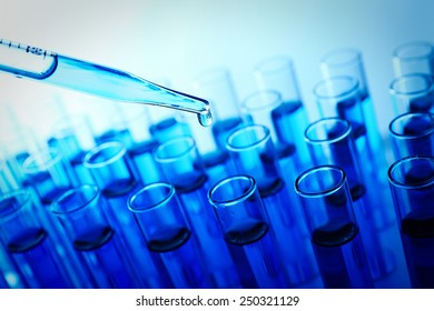 Pipette adding fluid to the one of test-tubes on blue background