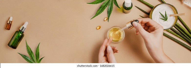 Pipette with CBD cosmetic oil in female hands on a table background with cosmetics, cream with cannabis and hemp leaves, marijuana. Flat lay, top view.