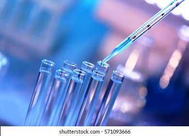 Pipette dropping a sample into a test tube, closeup - Shutterstock ID 571093666