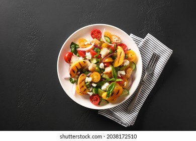 Piquant Panzanella with tomatoes, bread, cheese and peach in white plate on black background. Top view. Traditional Italian cuisine. Vegetarian panzanella salad. Mediterranean healthy food.