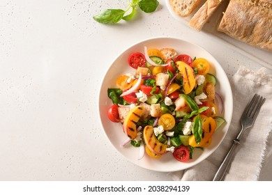 Piquant Panzanella with tomatoes, bread, cheese and grilled peach in plate on white background. Top view. Italian cuisine. Vegetarian panzanella salad. Mediterranean healthy food.