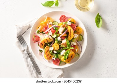 Piquant Panzanella with tomatoes, bread, cheese and grilled peach in plate on white background. Top view. Italian cuisine. Vegetarian panzanella salad. Summer vegetables colorful salad.