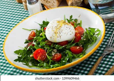Piquant salad of fresh arugula, cherry tomatoes and soft Italian cheese burrata with olive oil