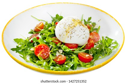 Piquant salad of fresh arugula, cherry tomatoes and soft Italian cheese burrata with olive oil. Isolated over white background