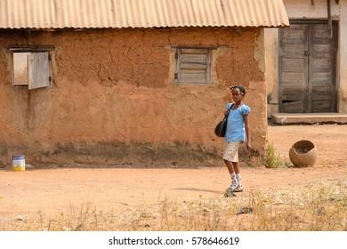 PIRA, BENIN - JAN 12, 2017: Unidentified Beninese little girl in a blue school uniform walk with a bag. Benin kids suffer of poverty due to the bad economy.