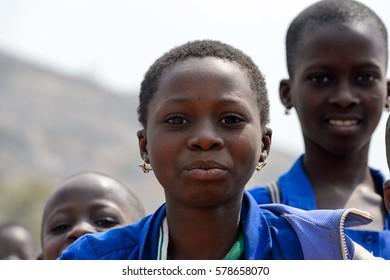 PIRA, BENIN - JAN 12, 2017: Unidentified Beninese little girl in a blue school uniform. Benin kids suffer of poverty due to the bad economy.