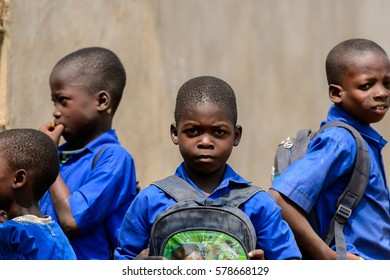 PIRA, BENIN - JAN 12, 2017: Unidentified Beninese little boy in a blue school uniform with a backpack. Benin kids suffer of poverty due to the bad economy.