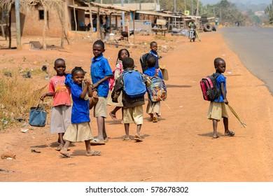 PIRA, BENIN - JAN 12, 2017: Unidentified Beninese children in school uniform go in the street. Benin kids suffer of poverty due to the bad economy.