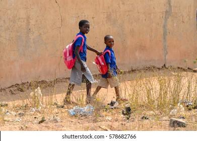 PIRA, BENIN - JAN 12, 2017: Unidentified Beninese little girls in a blue school uniform with backpacks. Benin kids suffer of poverty due to the bad economy.