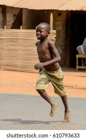 PIRA, BENIN - JAN 12, 2017: Unidentified Beninese little boy in mustard shorts runs on the street. Benin children suffer of poverty due to the bad economy.