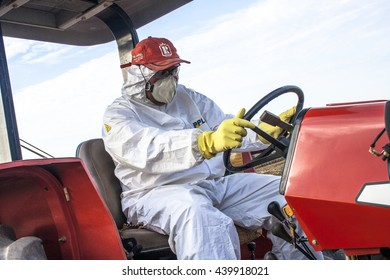 Piracicaba, SP, Brazil, 24/07/2008. Worker with Personal Protective Equipment drives a tractor that will make application of pesticide, in a plantation of sugarcane, in Piracicaba, SP.