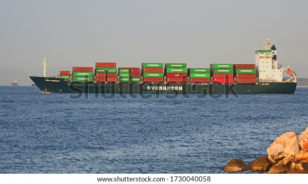 PIRAEUS, GREECE, MAY 12, 2020. Container ship EVERGREEN UNI-ASSENT, built in 1999, 165 meter long, departing from the port of Piraeus, Greece