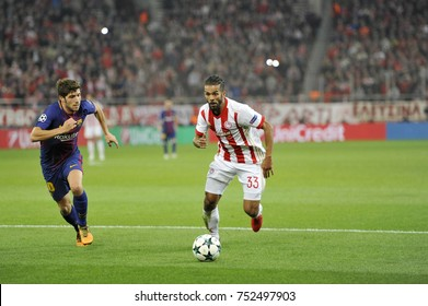Piraeus, Greece October, 31,2017. Olympiacos 's Mehdi Carcela-Gonzalez (33) with the ball and Barcelona's Sergi Roberto (20) in the champions league football match Olympiacos vs Barcelona in Piraeus.