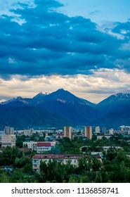 The piramidal mountain with rocks and ice in Tian Shan mountains over Almaty covered by clouds on dramatic dark sunset sky. Best place for active life, hiking and trekking. Best view from the window.