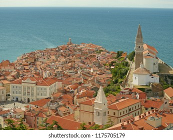 Piran, Slovenia - August 15, 2018: The view of Piran from the ancient city walls. St. George's Church dominates the skyline of this beautiful city on the Adriatic Sea.