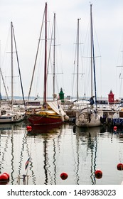 Piran, Slovenia, August 2019: sailing boats parked in the harbor of Piran and their reflection on the water