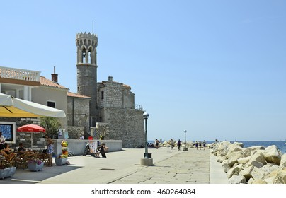 PIRAN, SLOVENIA - JULY 04: Unidentified people on promenade and medieval church Sveti Klementa in the pictoresque village on Adriatic sea, on July 04, 2015 in Piran, Slovenia
