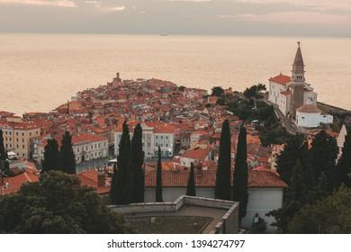Piran, Slovenia - July, 2018: Oval-shaped main Tartini square, old stone houses, narrow streets, port and small boats in Piran, Slovenia