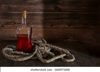 pirate bottle on the table, old rope, rum or whiskey in a transparent bottle, wooden background