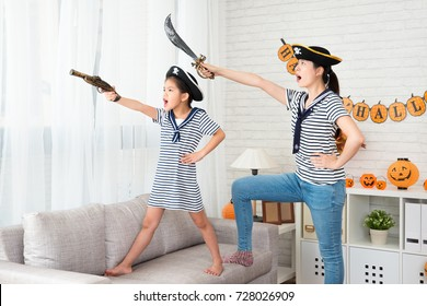 pirate costume girl and her mother play Halloween game and holding knife aim to window outdoor the direction in the living room at home