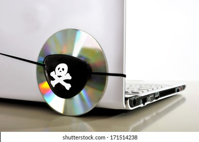 Pirate Eye patch on cd or dvd disk and computer representing piracy, illegal download and copyright violation