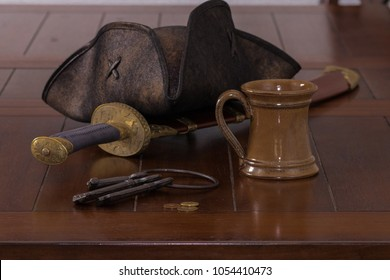 Pirate hat, sword, keys, and mug on wood table