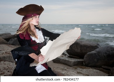 A pirate holds up a map on the beach