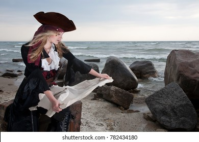 A pirate inspects a map on the beach