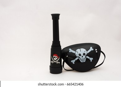 pirate jolly roger eye patch with black skill and cross bones mini telescope on a white background