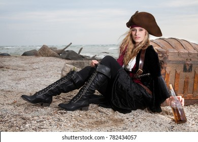 A pirate rests against treasure on the beach with rum
