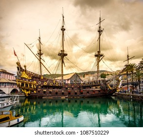 pirate sailing ship galleon sailer in the port of Genoa under a yellow storm cloudscape - Liguria - Italy .