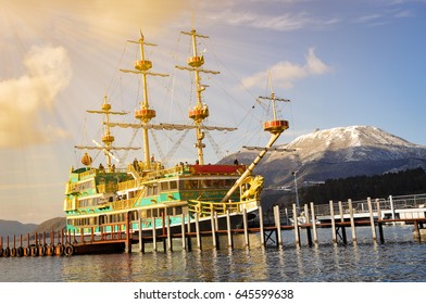 Pirate ship sightseeing in port near the sea with snow mountain and gold light sky background.