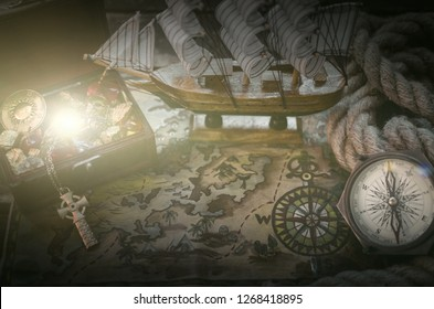 Pirate ship, treasure map, rope, treasure chest full of gold and a compass on a wooden table background.