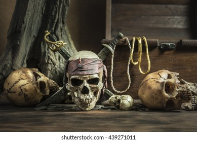 pirate skull with two swords and treasure coffer over three head of human background still life style