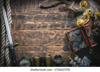 Pirate treasure chest with ancient coins and other various pirate equipment on flat lay table background.