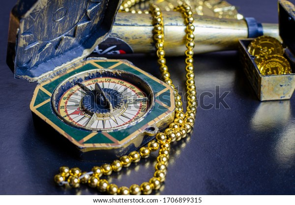 pirate treasure chest, close-up of a gold pirate medallion with a necklace