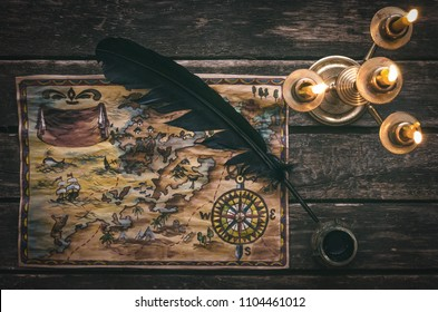 Pirate treasure map, burning candle, feather pen and inkwell on wooden ship table background.