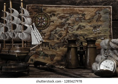 Pirate treasure map, compass, pocket watch, mooring rope and binoculars on a pirate captain table background.