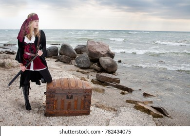 A pirate woman leans on a treasure chest as she watches the sea