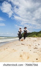 Pirates a man and a woman run along the sandy shore