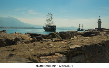 Pirate-style ships and a lighthouse off the coast of Alanya. Sea and mountains on the horizon. Alanya, Antalya district, Turkey, Asia