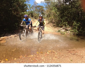 Pirenopolis, Goias, Brazil - January 18, 2017: Mountain bike racing. Cyclist crossing the river during a MTB champion.