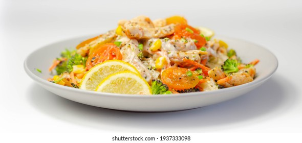 Piri piri style chicken on a bed of wholewheat pasta and vegetables, with a cool sour cream and chive dressing, tasty and healthy meal on the white background